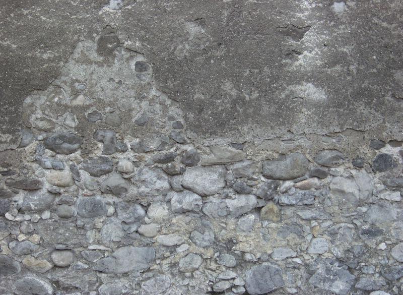水泥脱落漏出里面的石子石墙背景