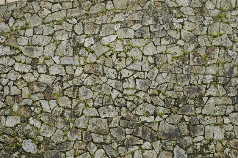 石头缝长了绿草的石头墙背景