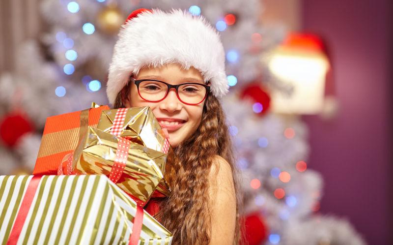 微笑的小女孩抱着圣诞礼物