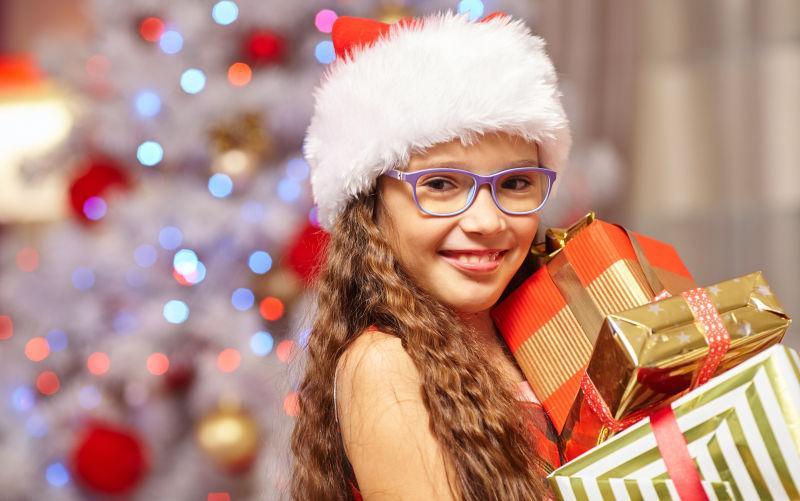 圣诞树前抱礼物的小美女