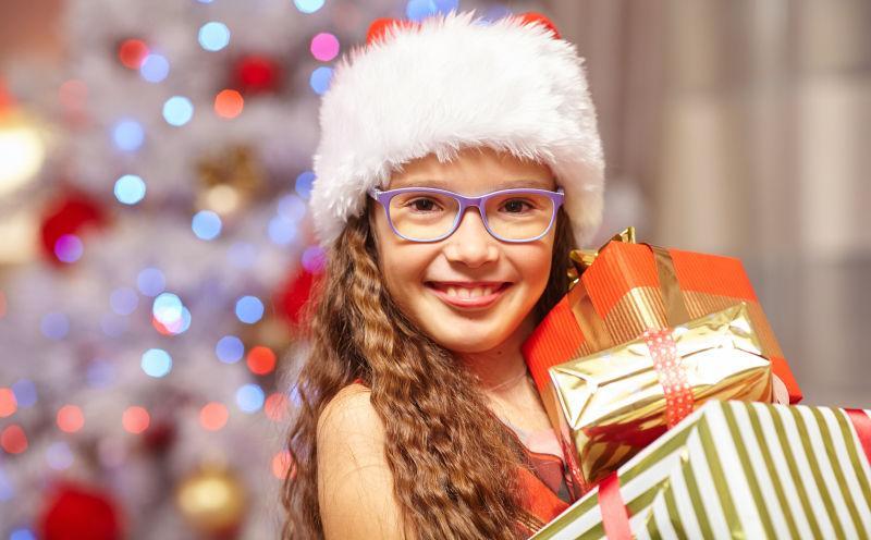 在圣诞树前拿着礼物的微笑女孩