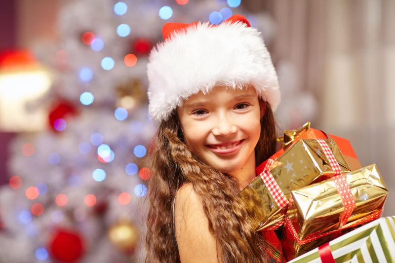 圣诞树前拿礼物的微笑女孩