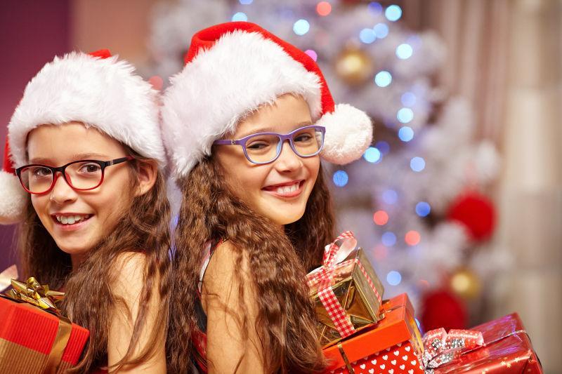 圣诞树前拿礼物的快乐姐妹