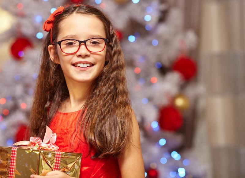 圣诞树前拿礼物的女孩