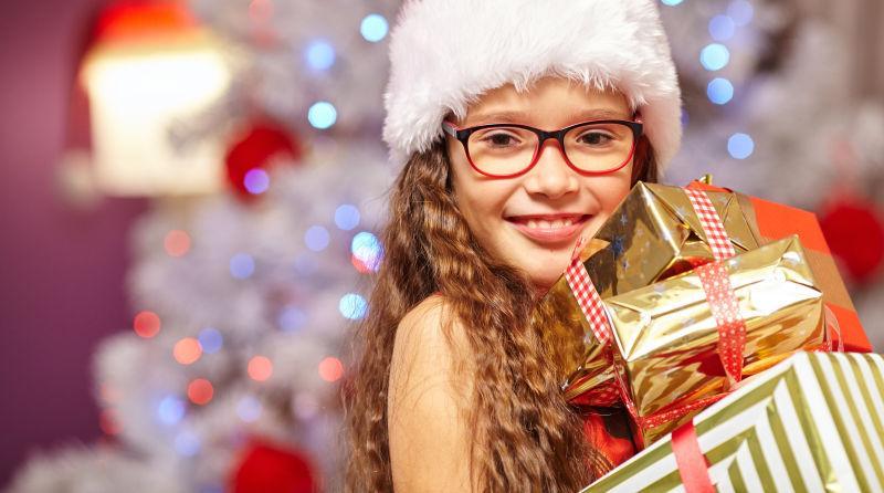 在圣诞树前微笑的女孩拿着礼物