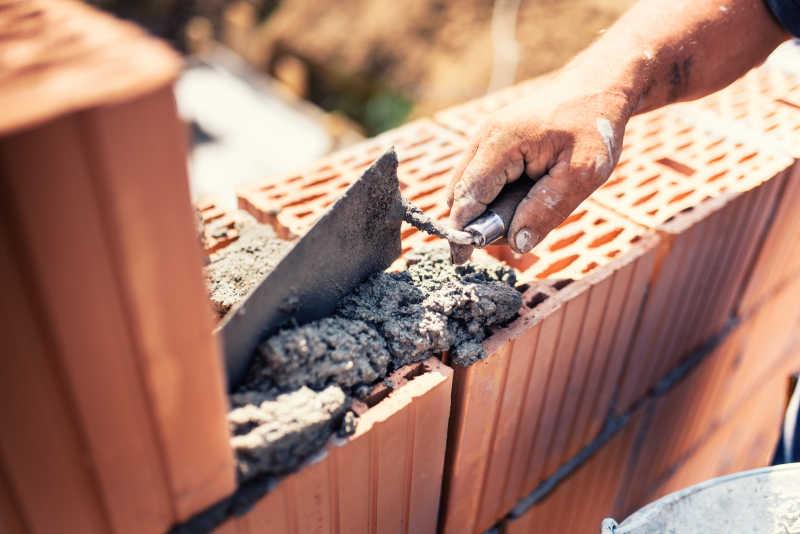 建筑瓦工工人使用腻子刀铺砂浆
