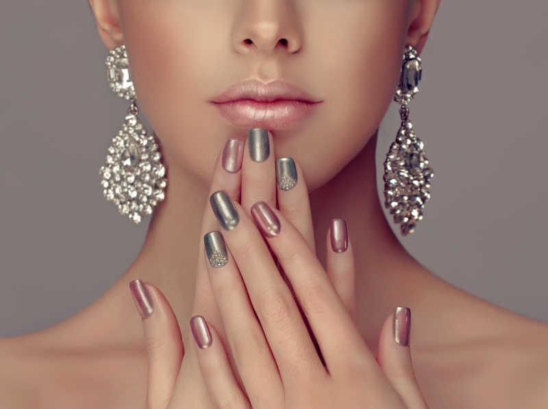 带着钻石耳环涂着漂亮指甲冒着下巴的优雅少女