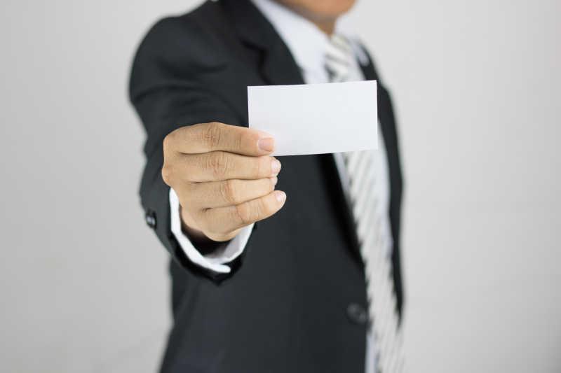 一个穿西装站着的人手拿白色名片