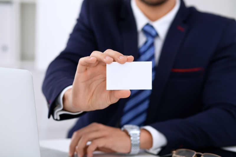 坐在桌旁给名片的商人或律师的特写镜头