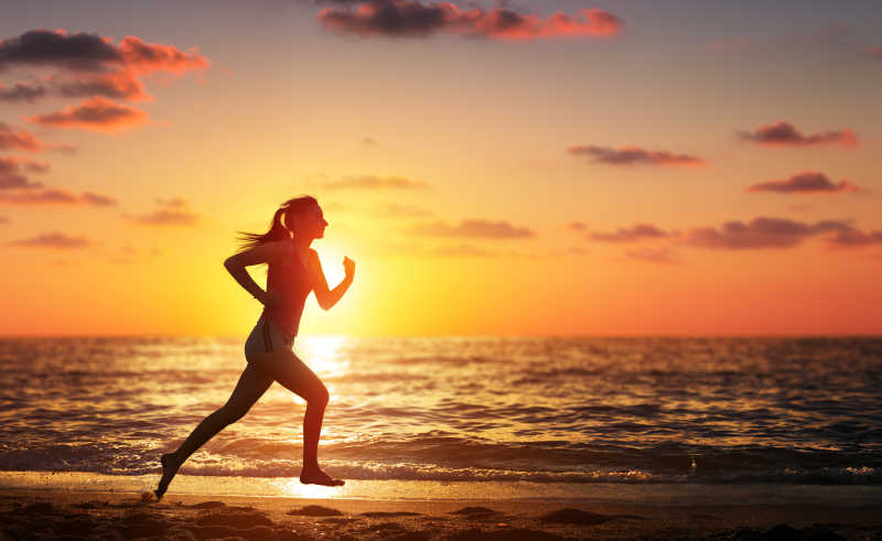 日落时分在海滩奔跑的赛跑女子