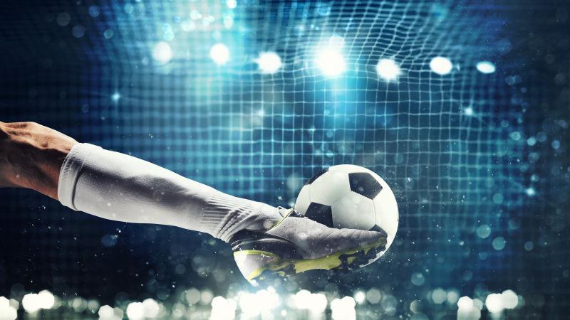 足球前锋准备将球踢入足球球门的特写镜头