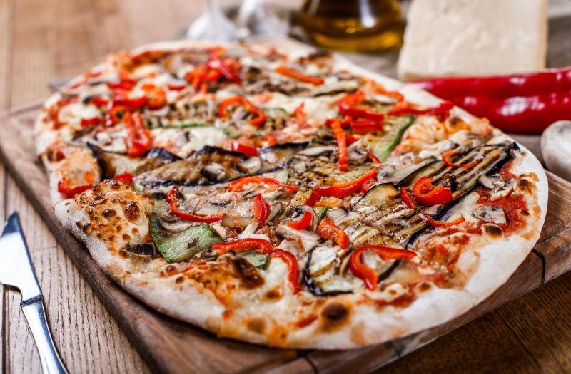 美味的比萨饼-鸡肉、西葫芦、茄子、胡椒、奶酪和蘑菇放在木制的乡村餐桌上-调色