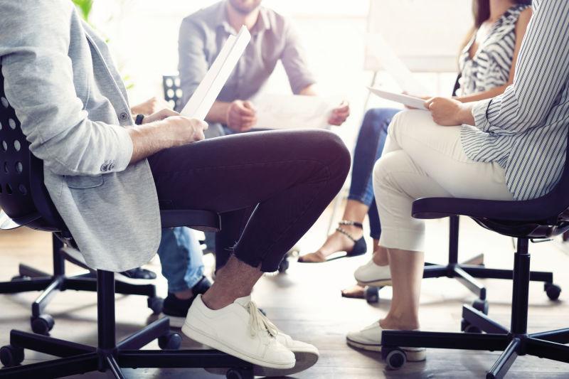 团队合作是成功的关键-穿着时髦休闲装的商务人士在办公室举行头脑风暴会议时谈笑风生