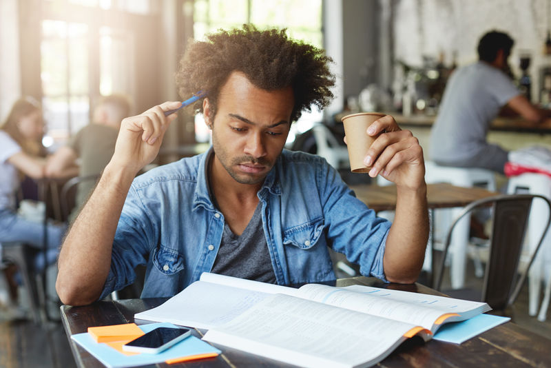 专注体贴的黑人欧洲学生,留着非洲式发型,用笔挠着头,在咖啡馆喝着热茶,在大学里准备法语课,翻译课本上的文章。