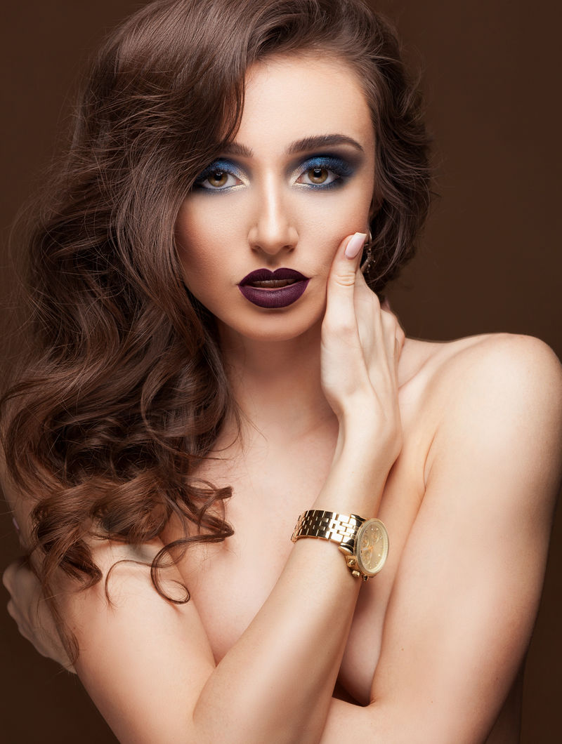 迷人的Elgant女士,专业化妆,卷发冰雹,手臂上戴着时尚手表。