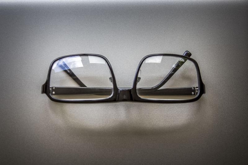 一副黑色方形框框边眼镜-放在白色长凳上-白底白光环绕