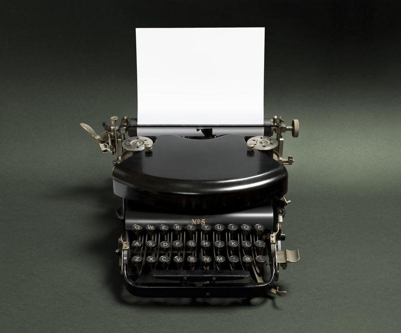 黑色背景的老式打字机-一种集成在黑色背景上的古打字机的低调版本-在白页上留有文本空间-复制空间上的灯光效果