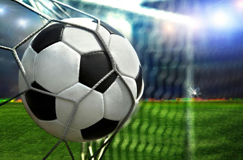 足球在对手的球门上得分-一名足球运动员在体育场的球门上得分