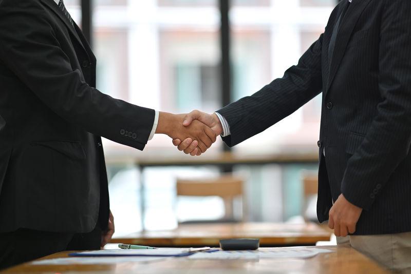 商务人士在会议室结束会议时握手