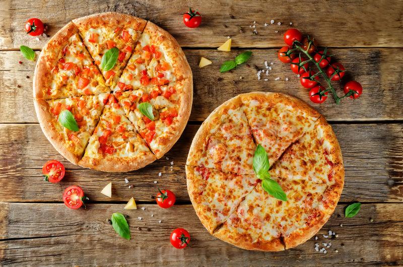 比萨配奶酪、鸡肉和新鲜的番茄片-以木材为背景-调色-选择性聚焦