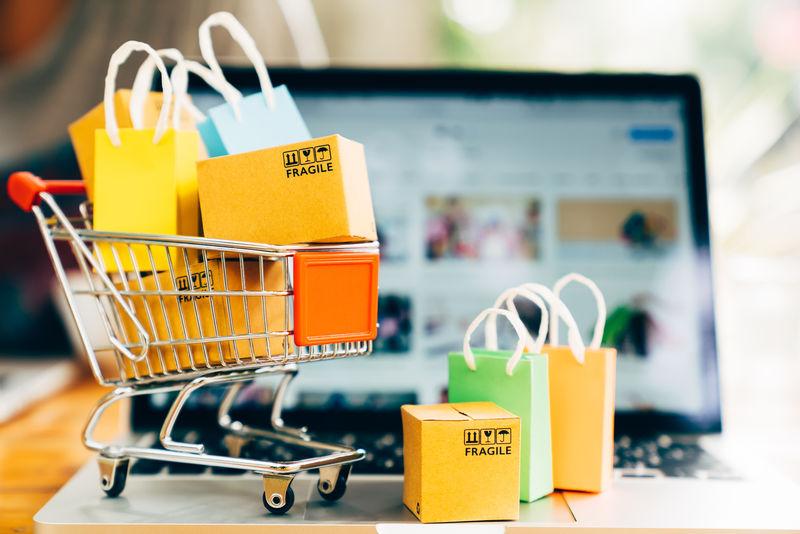 购物车中的产品包装盒和购物袋-带有笔记本电脑-网络商店在屏幕上购物-提供在线购物和配送概念