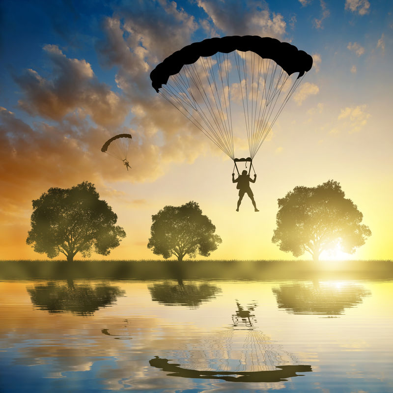 在日落时降落的跳伞者侧影