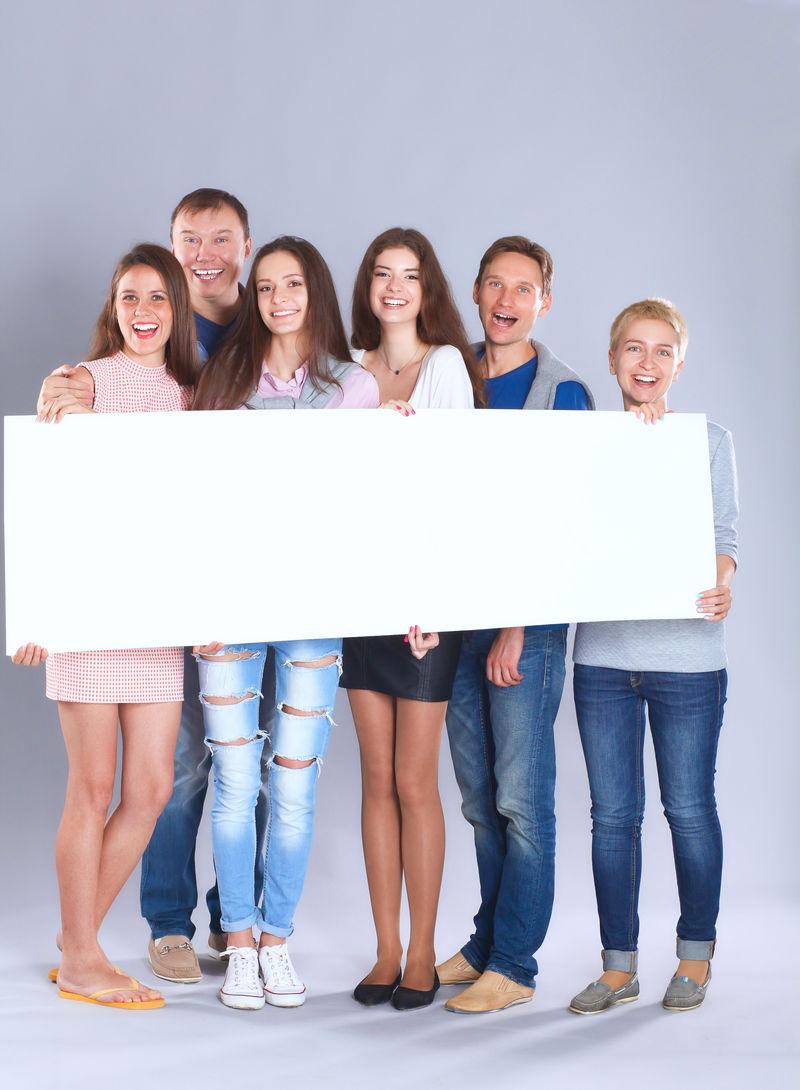 一群快乐的年轻人站在一起,手握空白