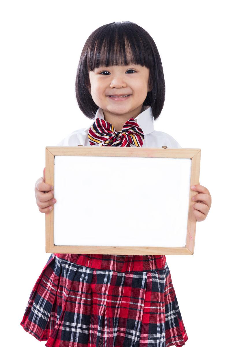高高兴兴的亚裔中国小女生拿着白板