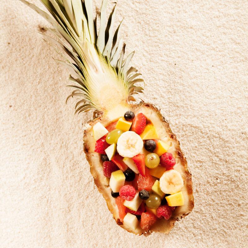 新鲜异国情调热带水果沙拉,配半个菠萝,在夏季阳光下呈白色纹理,从头顶观看。