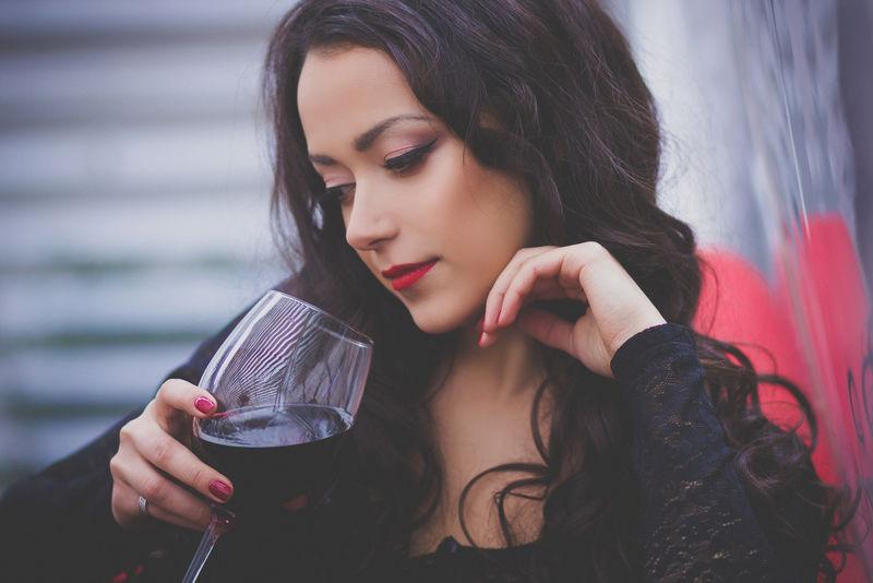美丽的长发女人在餐馆里喝红酒。酒精,美极了。