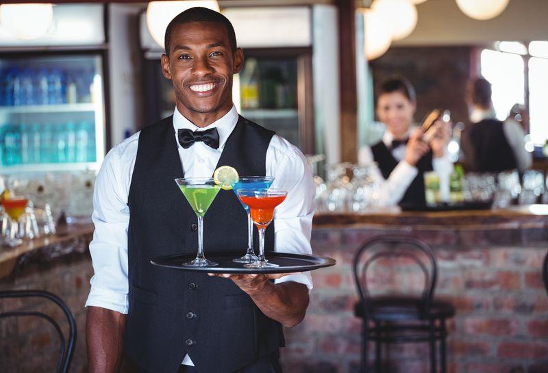 酒保拿着鸡尾酒杯的托盘的画像