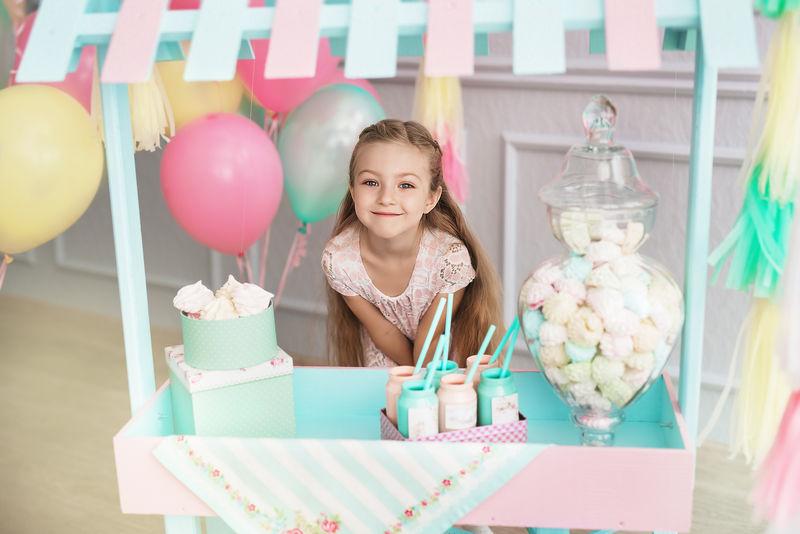 美丽的小女孩站在玩具糖果店后面