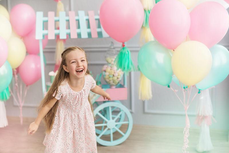 小女孩在一个装饰许多气球的工作室里大笑