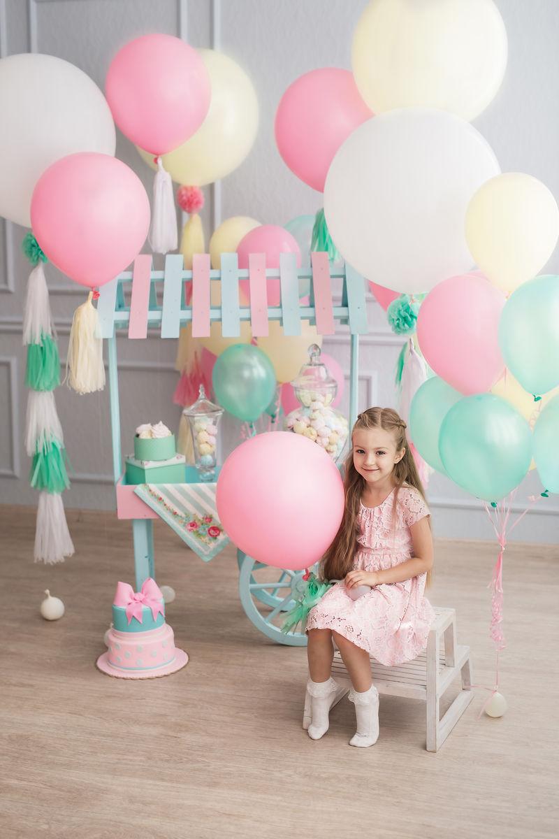 一个小女孩坐在一个装饰着彩色彩铃的房间里。