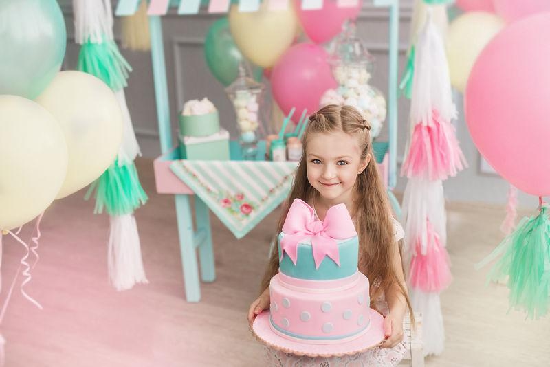 小女孩在装饰房间里拿着一个大蛋糕