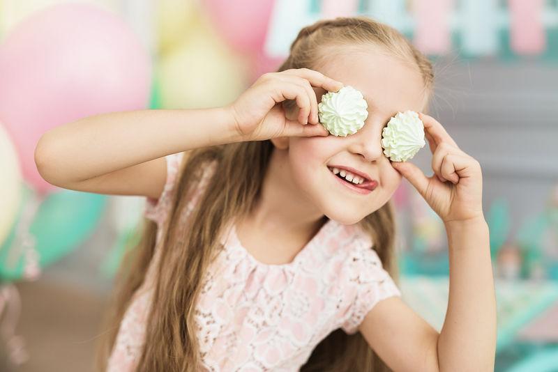 小女孩微笑着,把蛋糕放在他的眼睛上。