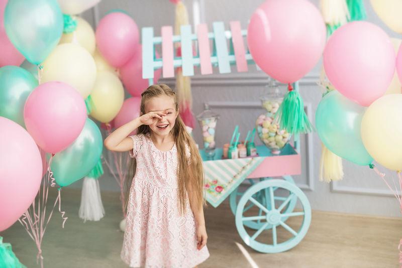 小女孩微笑着闭上眼睛在演播室里