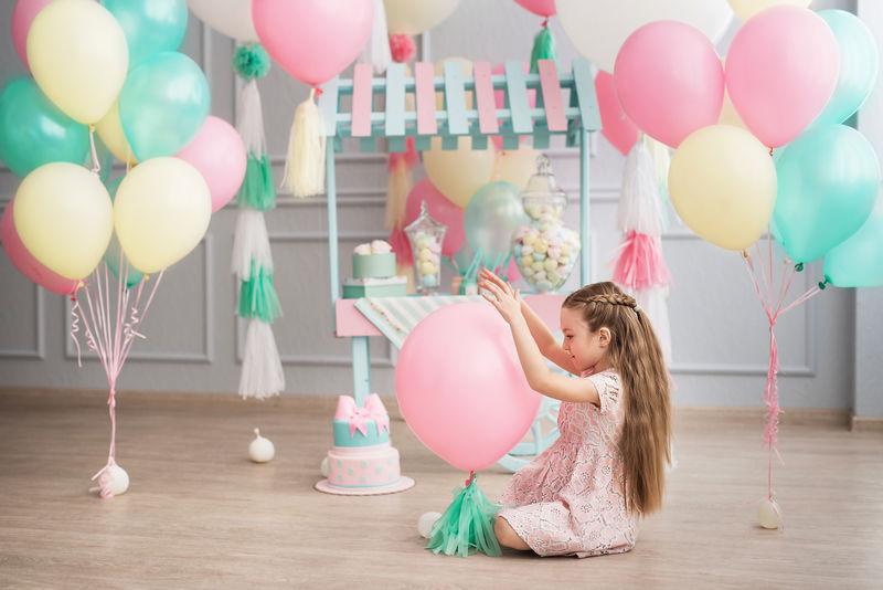 小女孩坐在一个装饰着彩色气球的工作室里