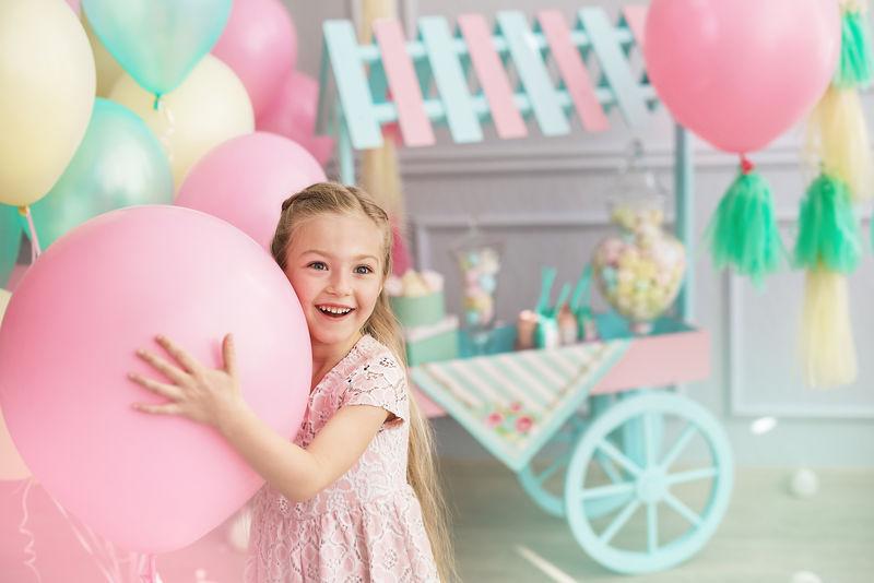 一个小女孩微笑着抱着一个大气球