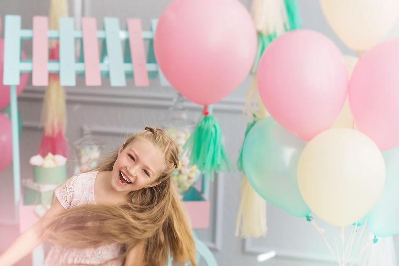 小女孩笑着跳上一个有气球的工作室