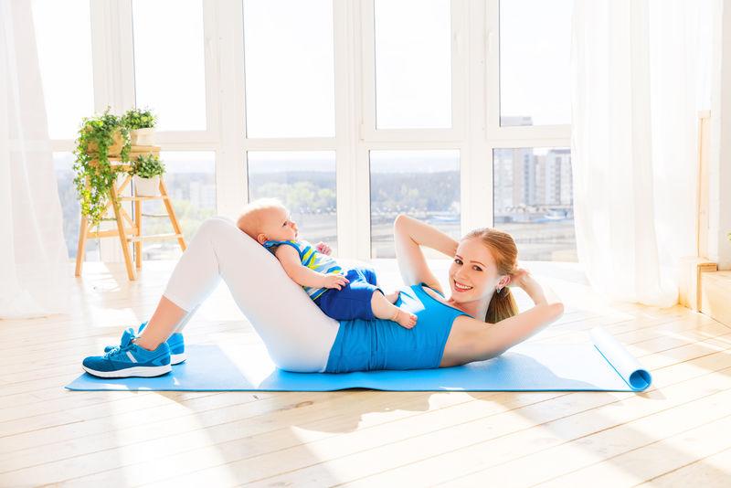 运动妈妈在家里和宝宝一起做健身和瑜伽。