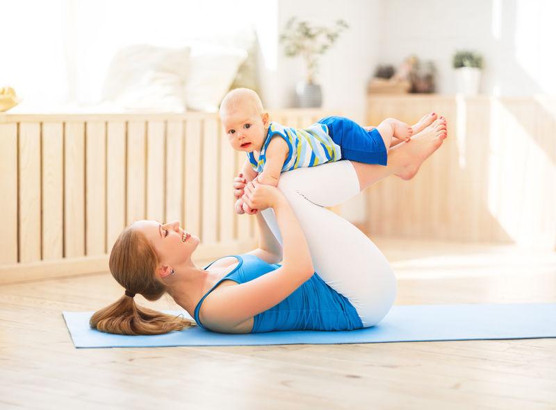 运动妈妈在家里和宝宝一起做健身和瑜伽