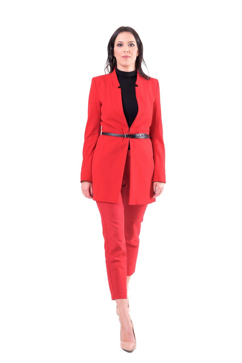 成功优雅的年轻女商人穿着红色时髦的西装行走。全身隔离在白色背景上。