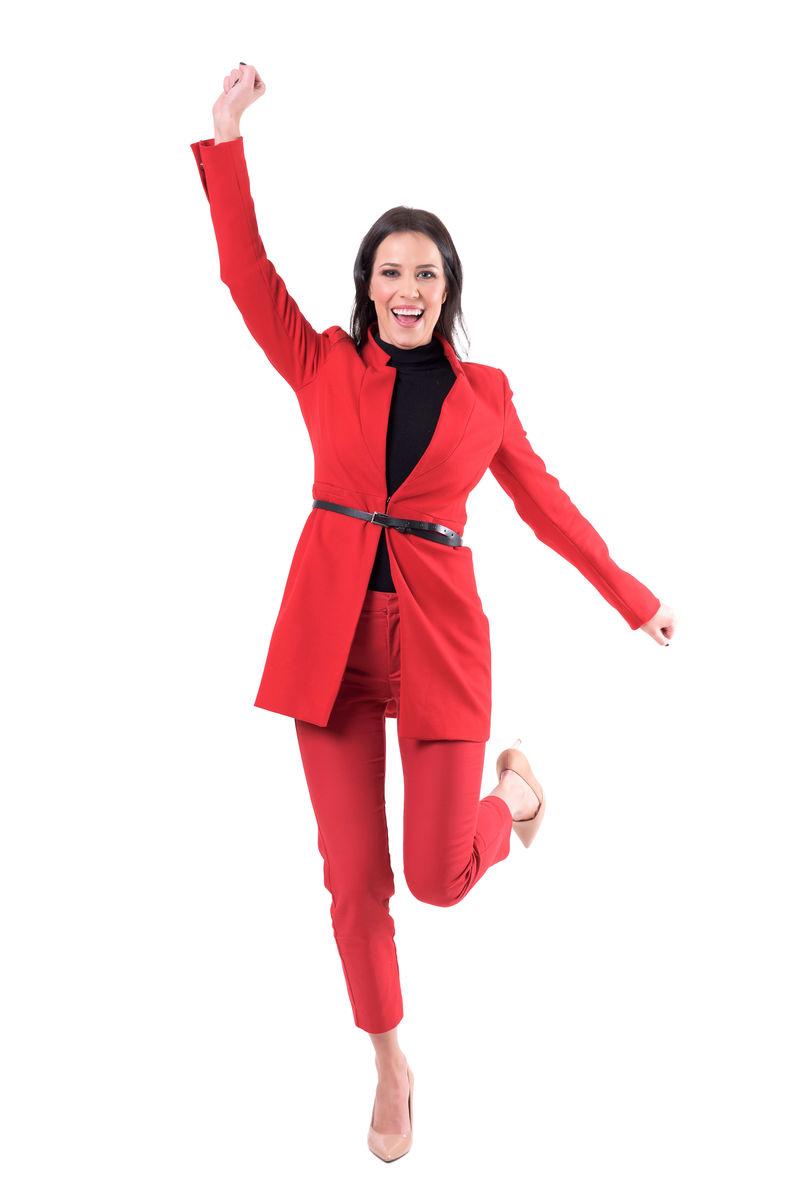 喜气洋洋的年轻优雅迷人的商务女性身着红色正装庆祝成功。全身隔离在白色背景上。