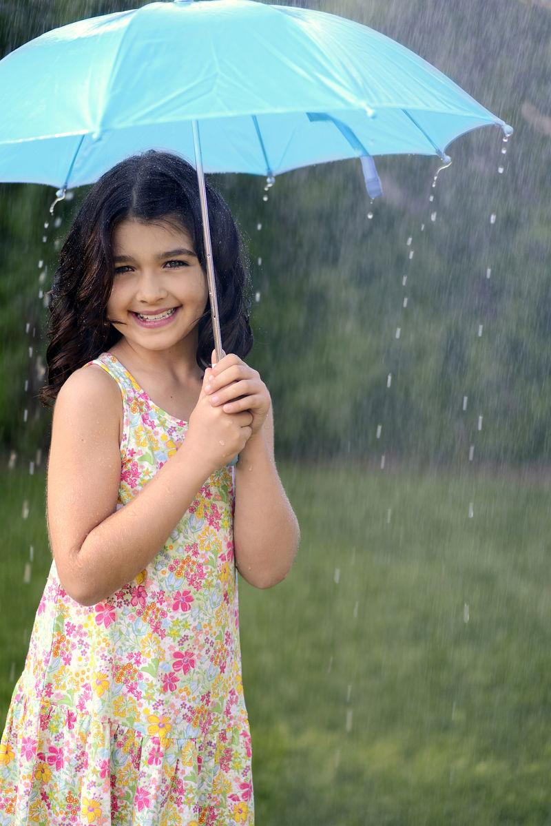 在雨中拿伞玩耍的小女孩