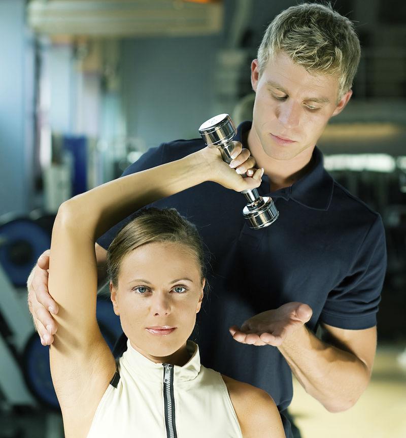 在私人教练的帮助下-年轻女子在健身房举哑铃