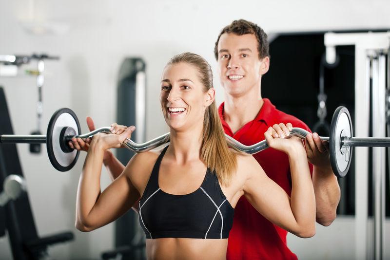 女子在健身房和私人健身教练用杠铃进行力量体操