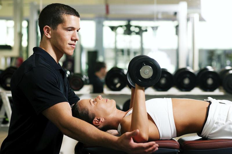 带着私人健身教练在健身房用哑铃锻炼的女人