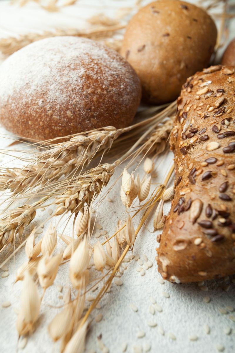 一张白色桌子上的乡村新鲜面包和小麦,特写镜头。