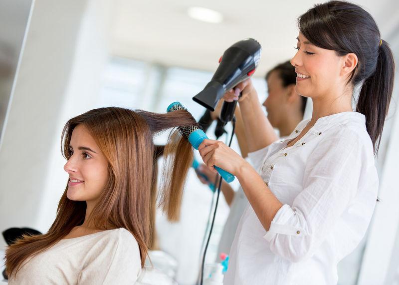 美容院女顾客的发型师在吹干头发